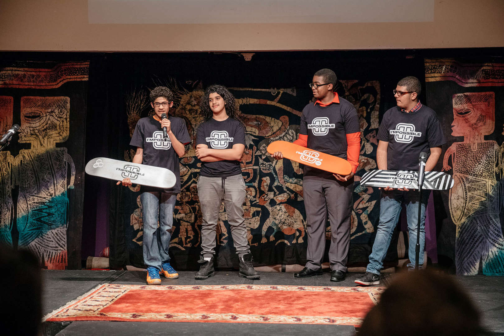 Students holding skateboards speak on stage