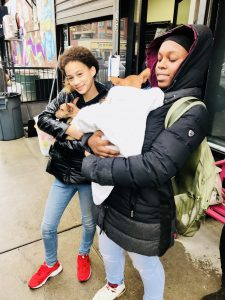 Two students cradling puppies in their arms on the street