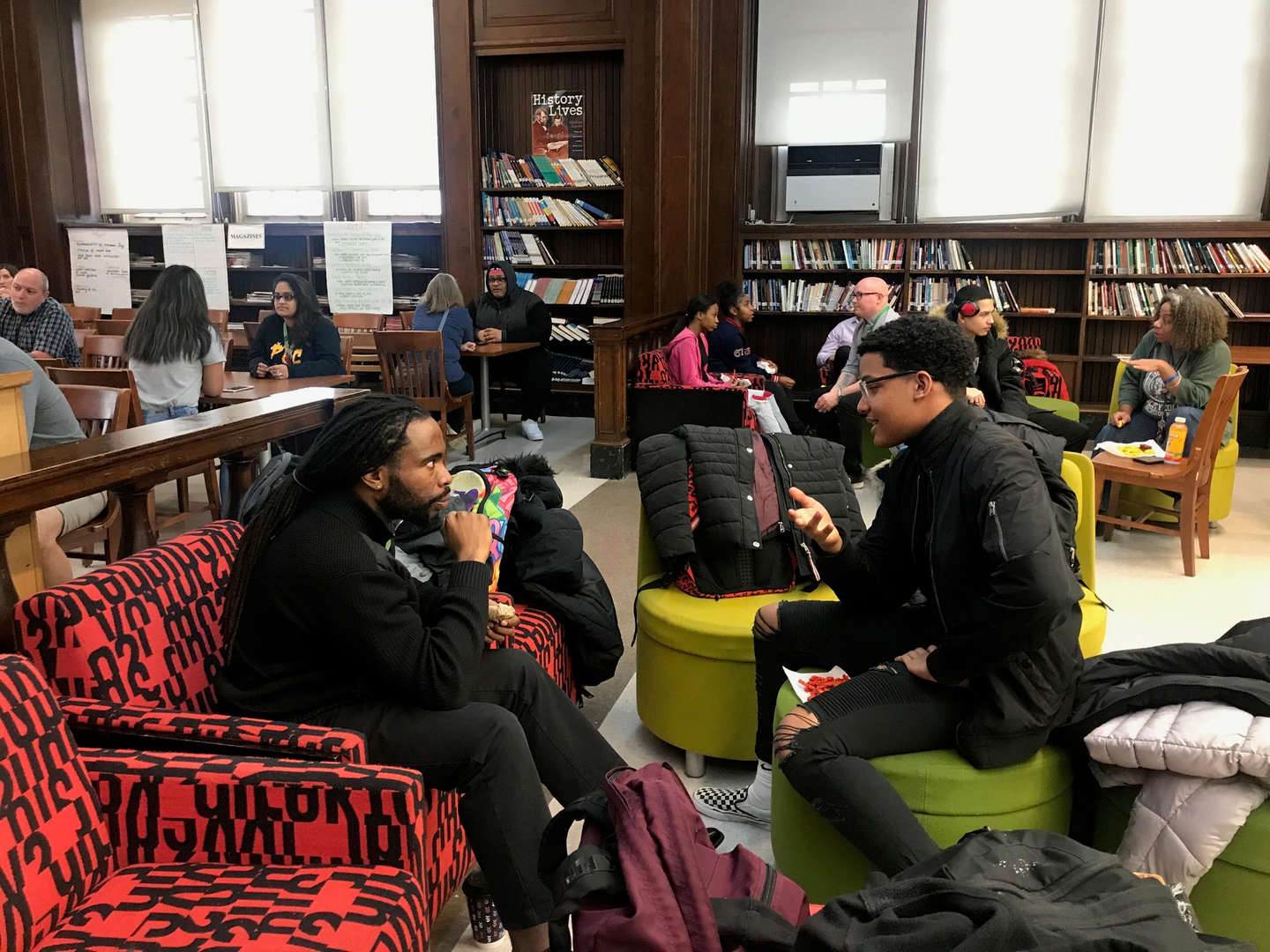 Student talks closely with an adult in the library