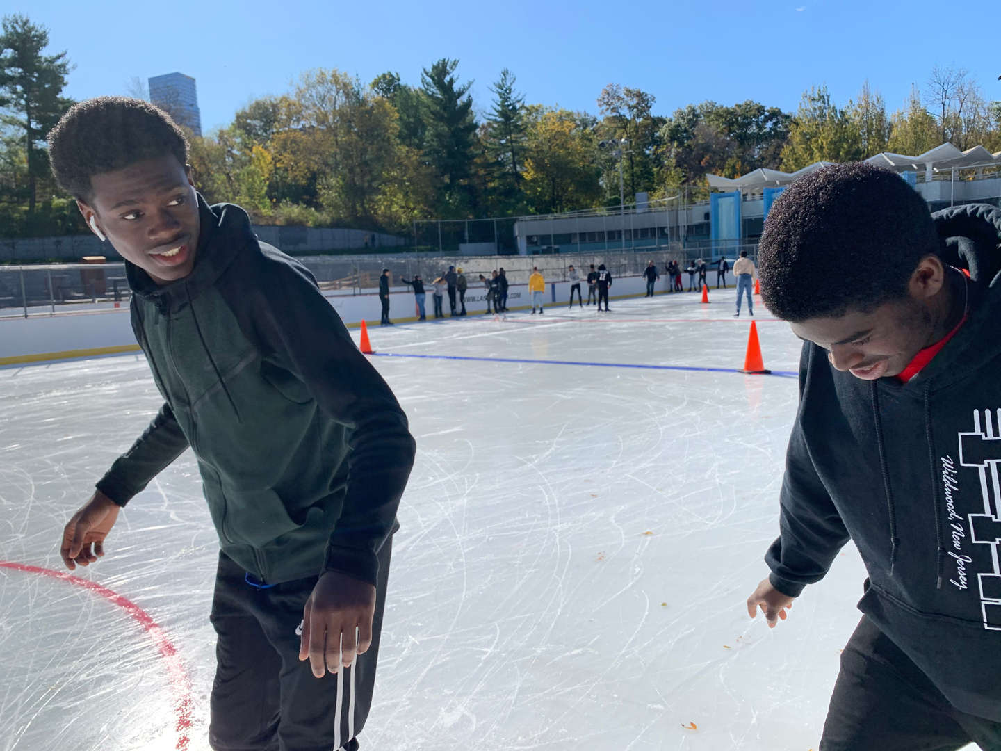 Two students watch out for each other as they skate side by side