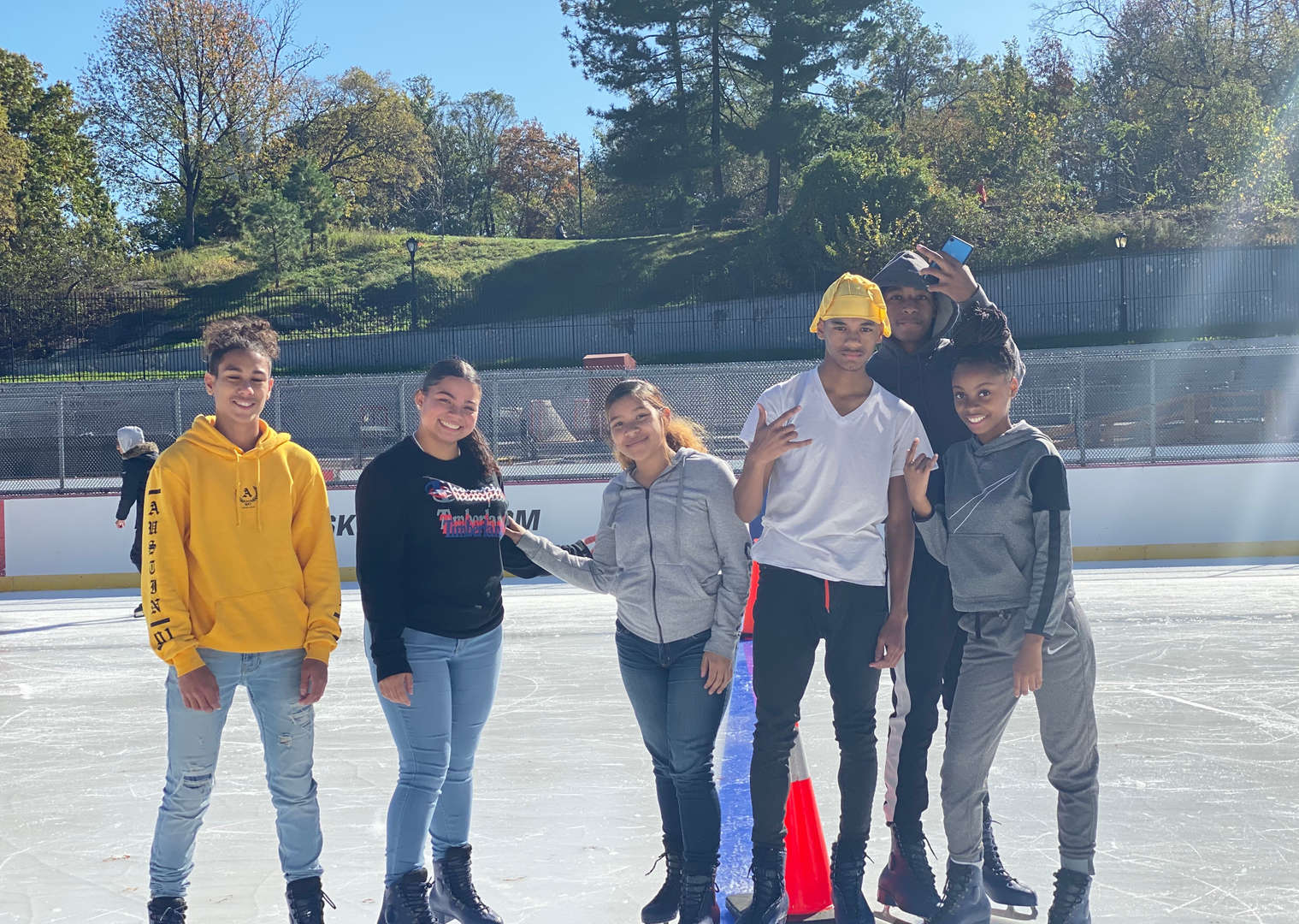 Six students stand in the sun on an ice skating rink