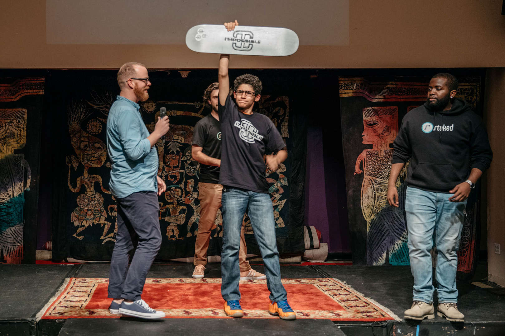 Student triumphantly holds up his skateboard on stage