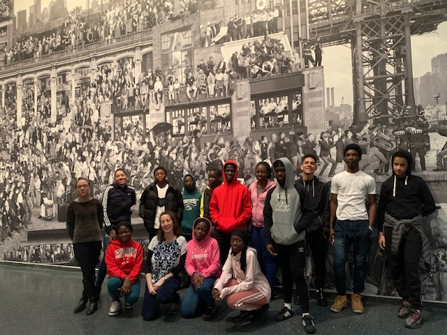 Students stand with their teacher in front of a wall-sized black and white image