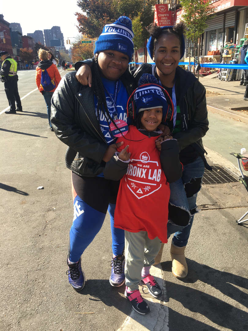 "Two women and a young boy in Bronx Lab t-shirts and ""volunteer"" beanies"