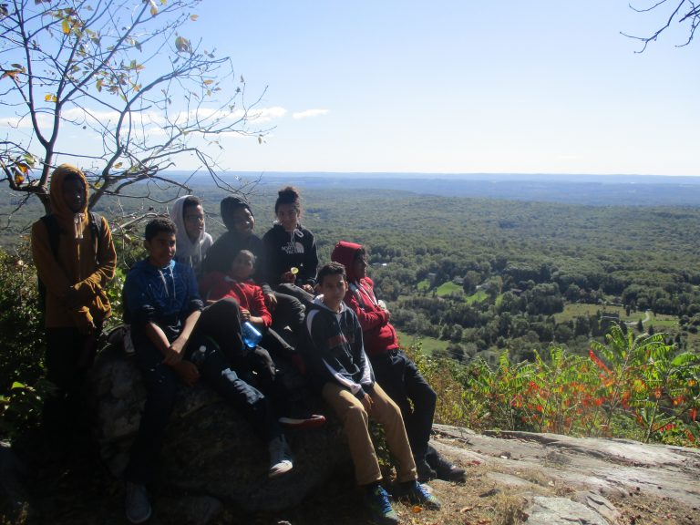 Students sitting on a rock overlooking a field of trees
