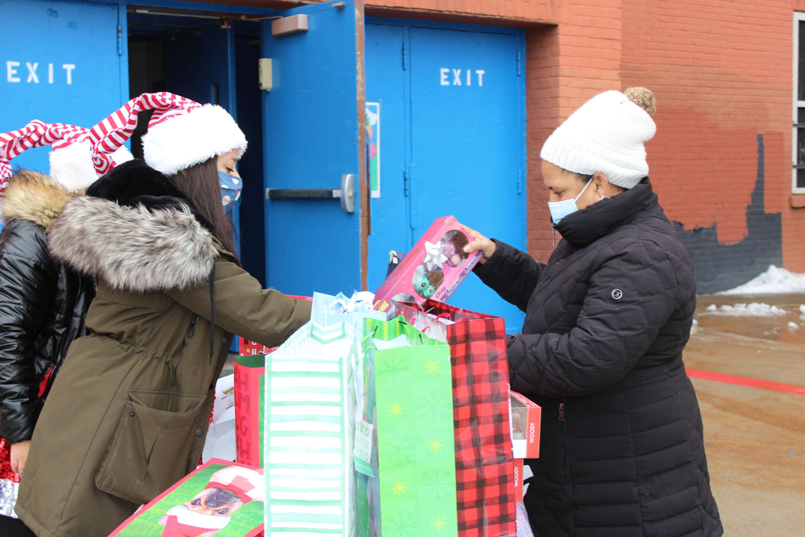 PS staff putting gift in a red and black gift bag to a parent
