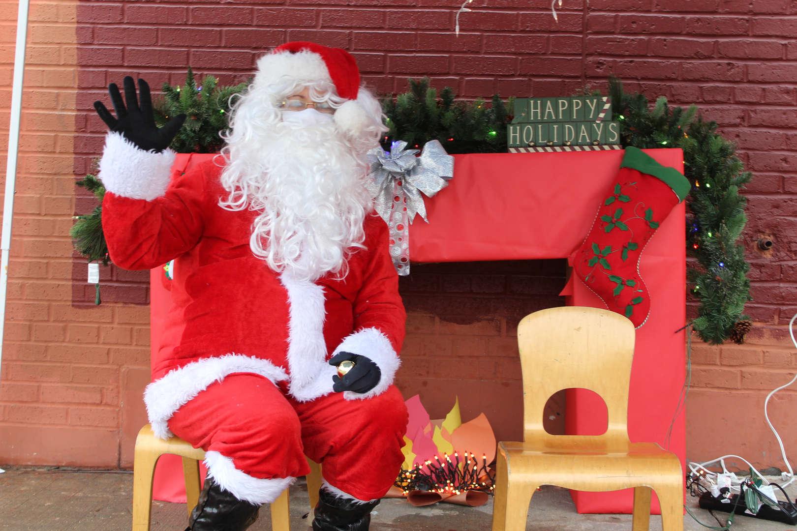 Santa sitting behind a fireplace.