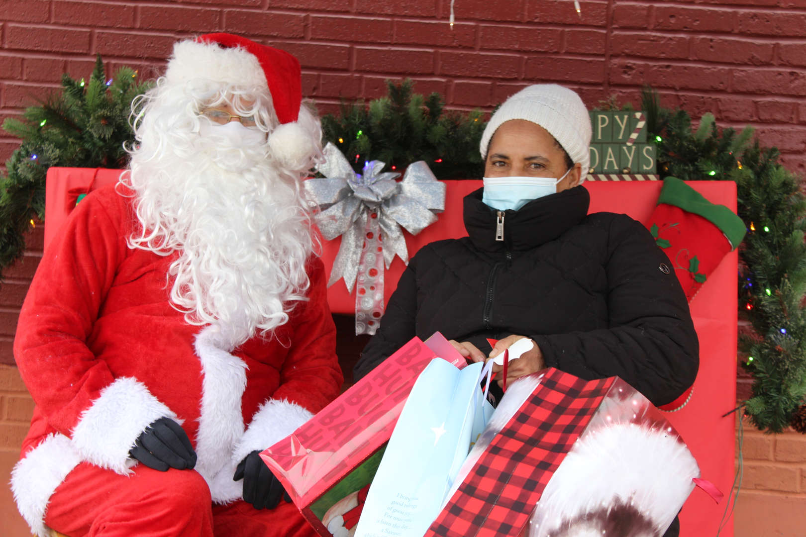 parent taking picture with Santa holding a red and black gift bag