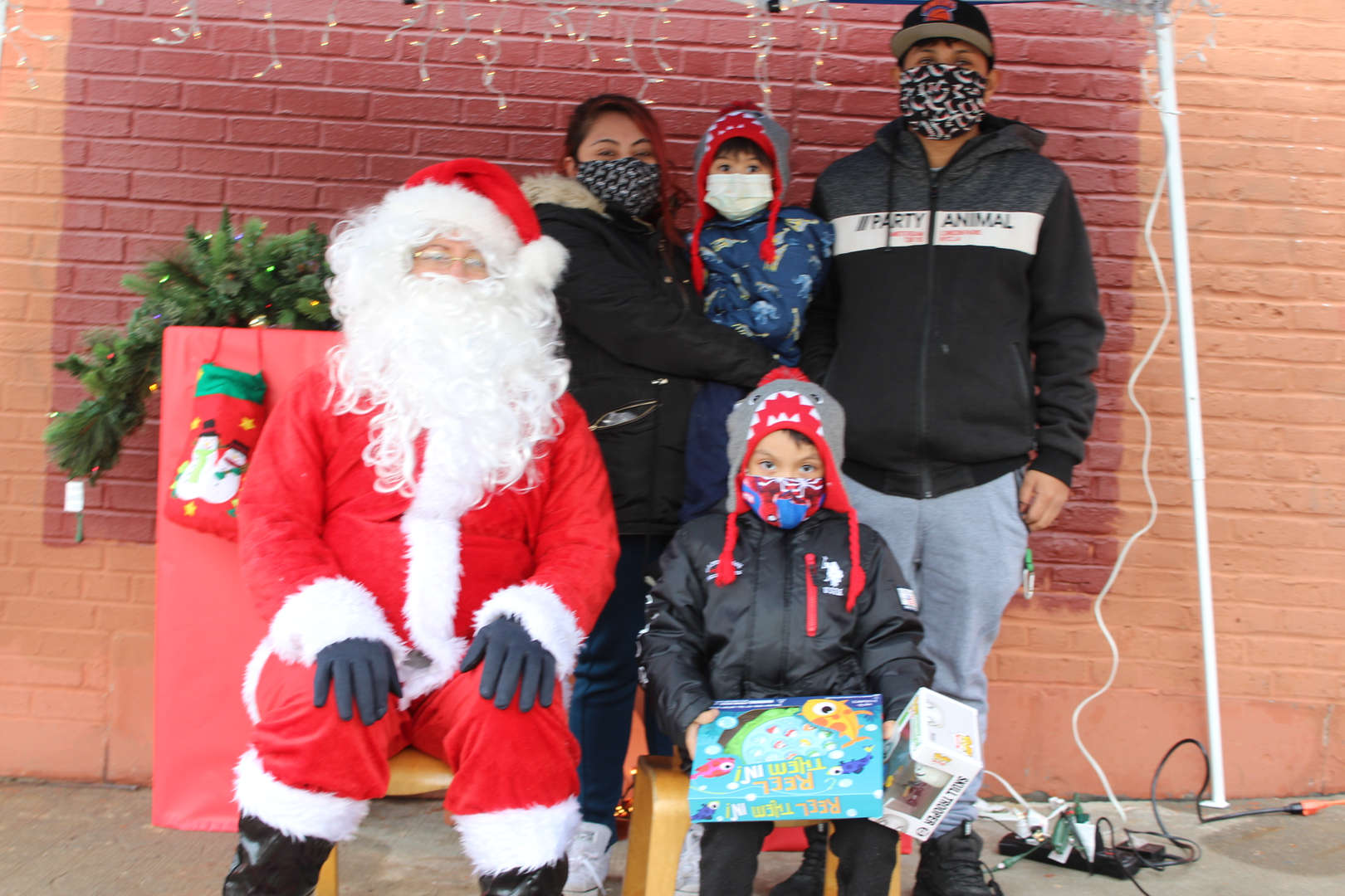 a ps 59 family taking a picture with Santa. Student holding his gifts