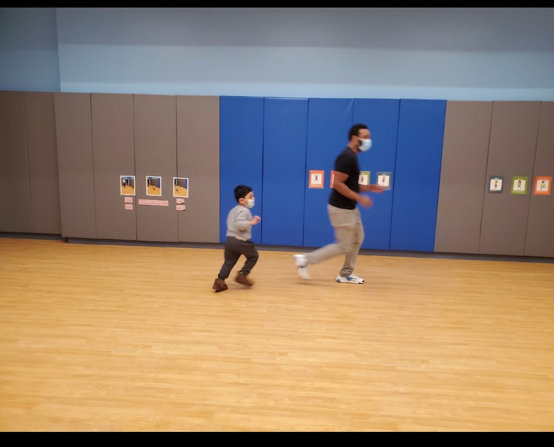 Pre-k student running with the physical education instructor in the gymnasium