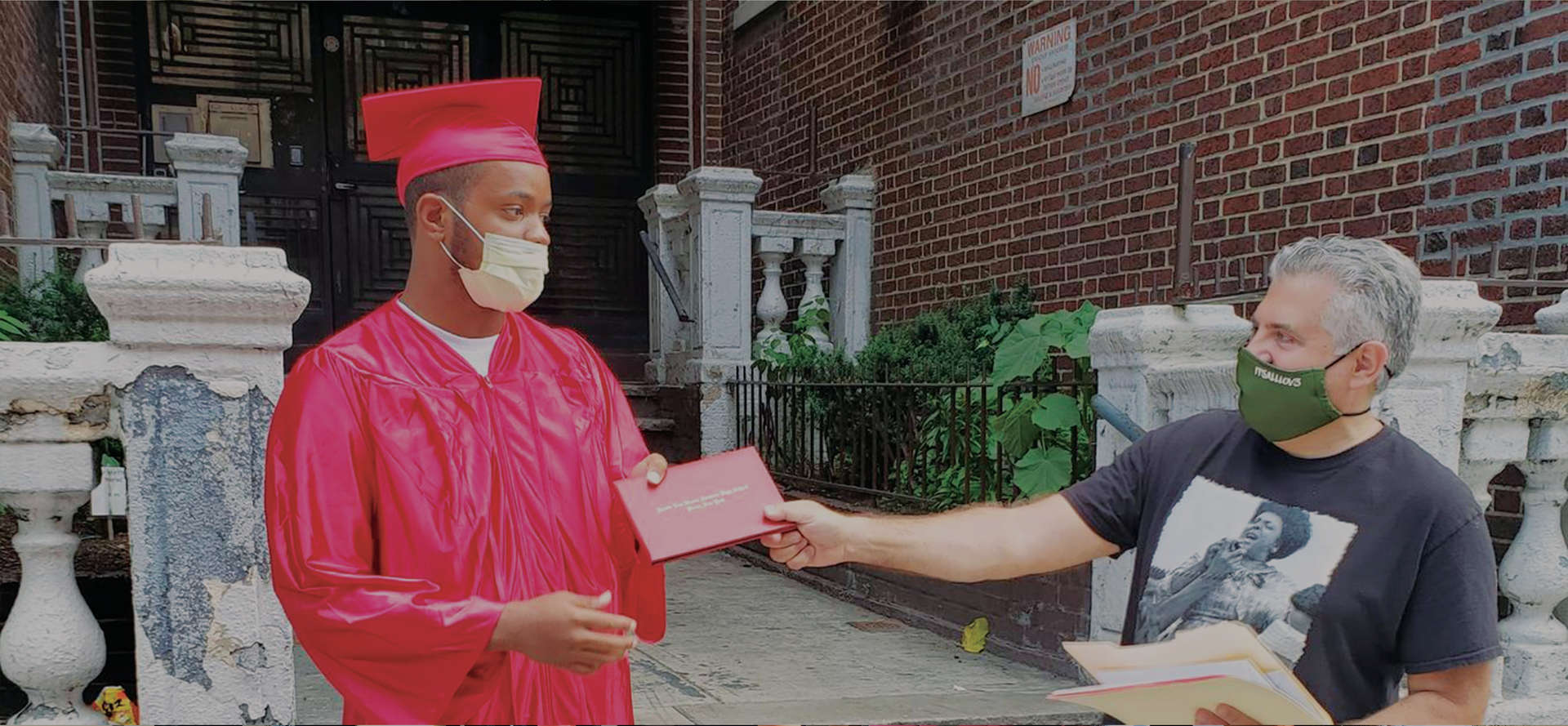 Student wearing a mask receiving a graduation diploma from his teacher