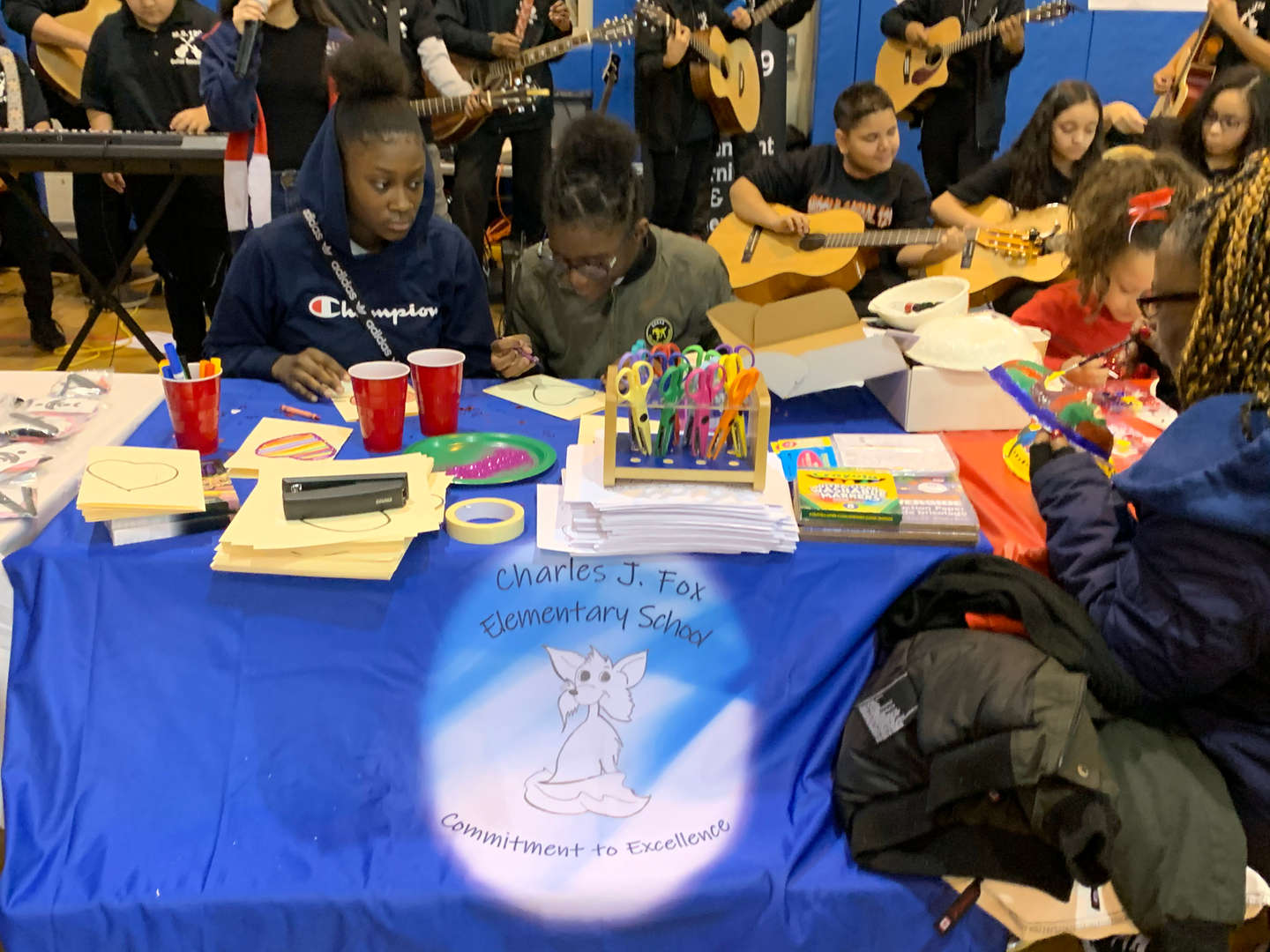 Students doing crafts at the Charles J. Fox Elementary School table