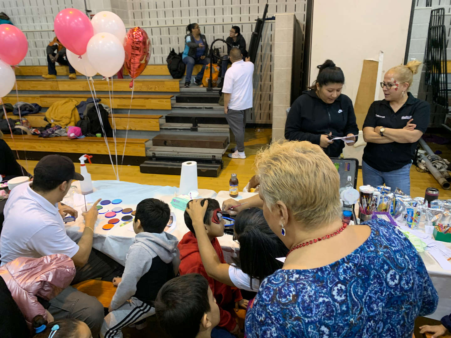 Students sitting along a table getting their faces painted
