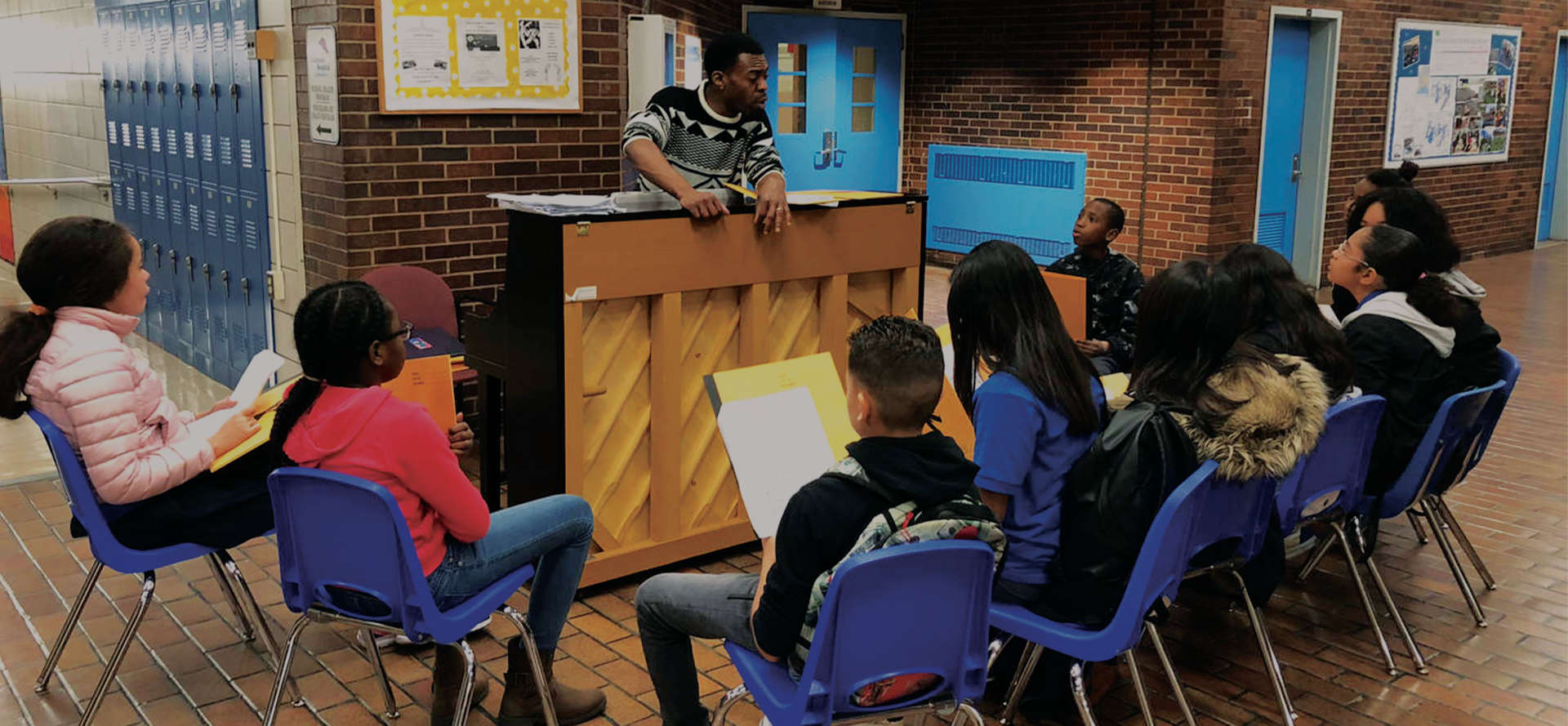Teacher leaning on a piano and speaking to his students