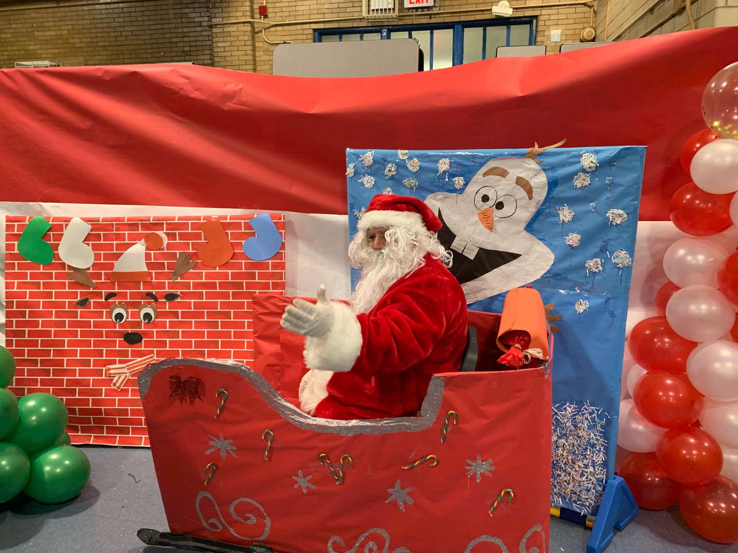 Santa beckons to a family in his sleigh