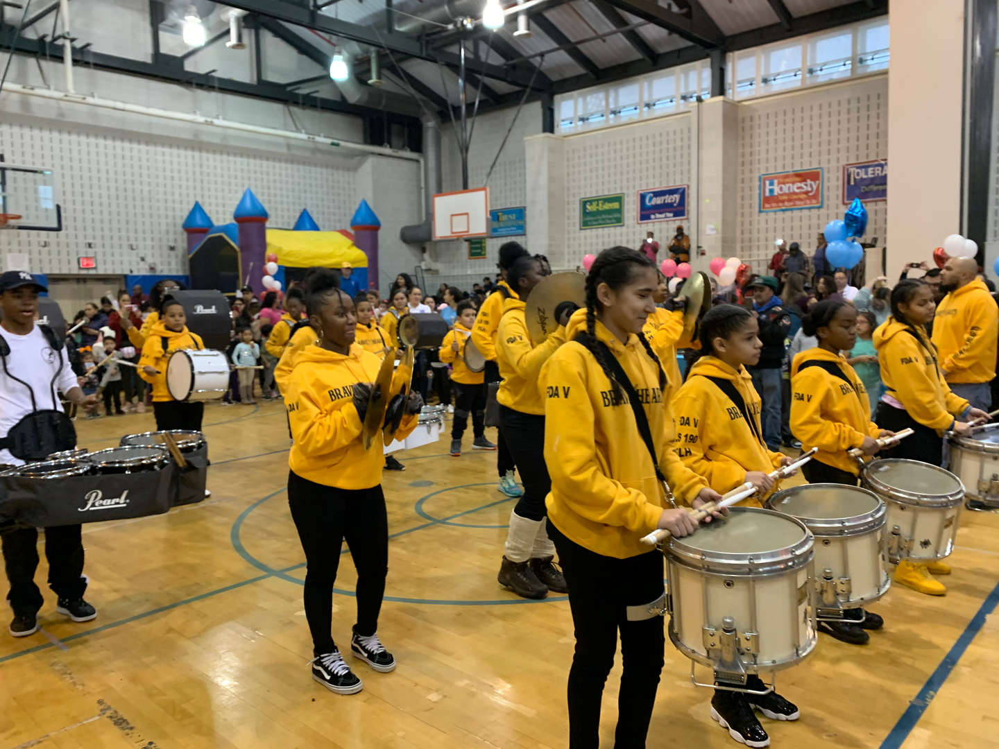 A marching band of students plays wearing matching yellow jackets