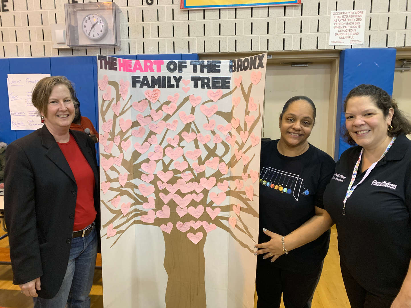 Three women holding up a craft board of the Heart of the Bronx Family Tree