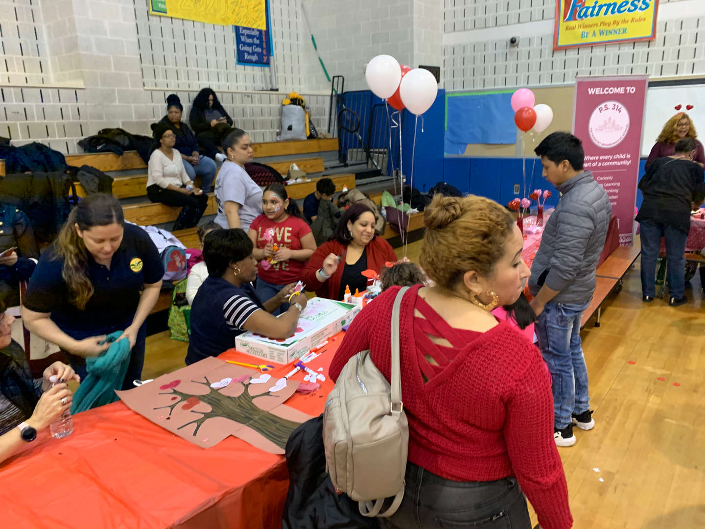 Parents and students standing around a long table with pink balloons