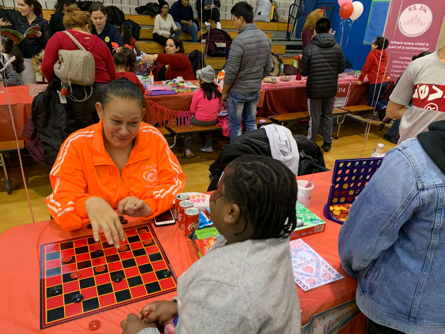 Student playing checkers with a woman