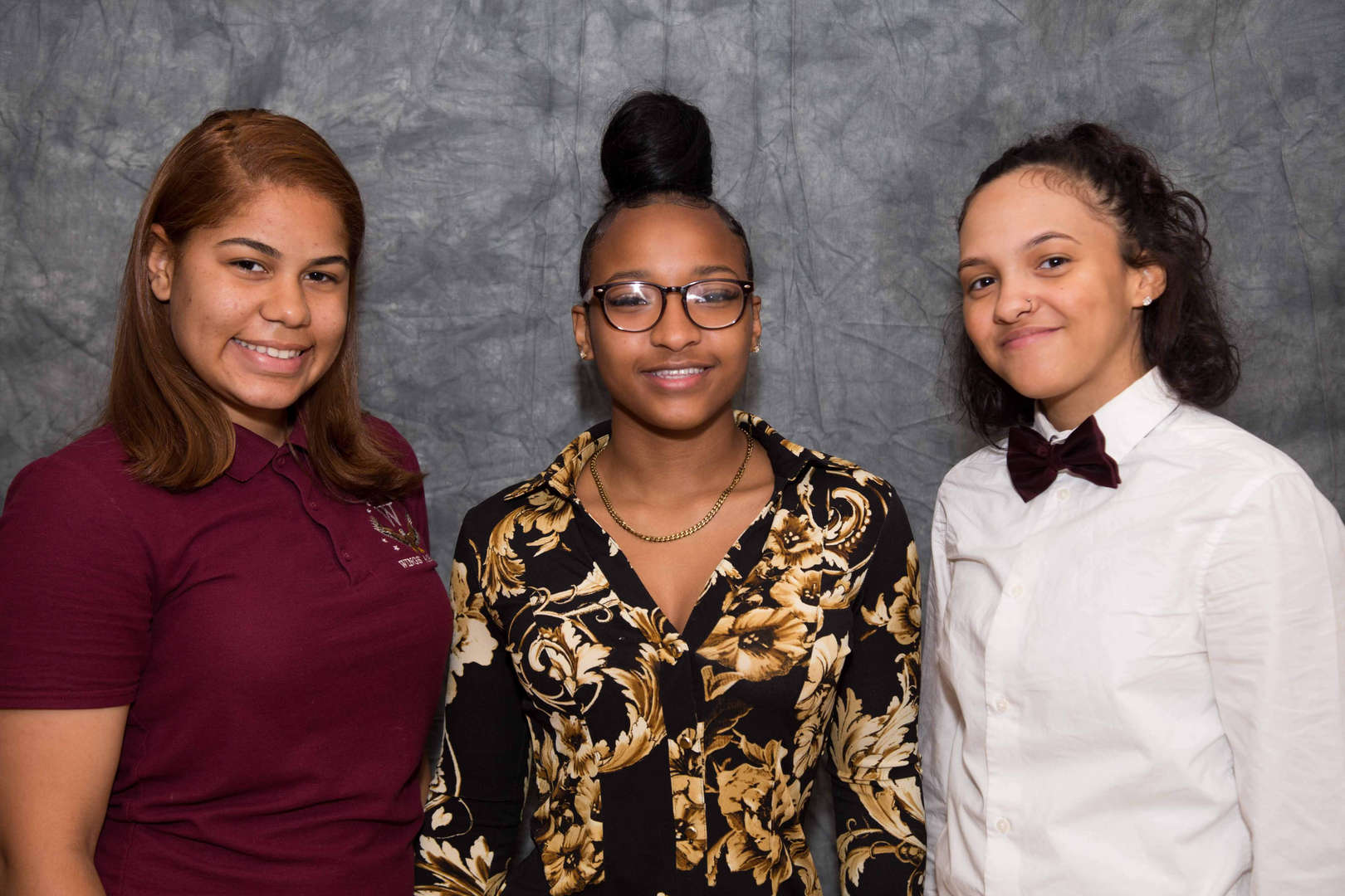Three students smiling together in front of a gray background