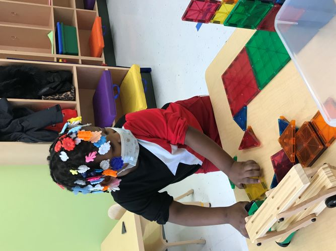 pre-k student playing with blcoks