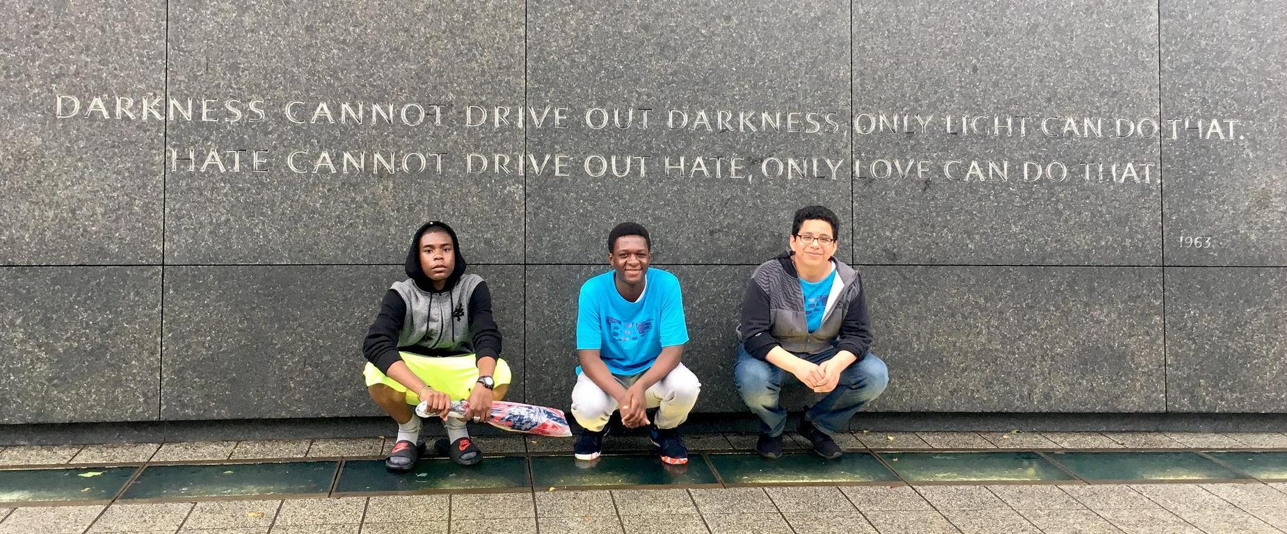 Three students crouched in front of a quote engraved in a marble wall