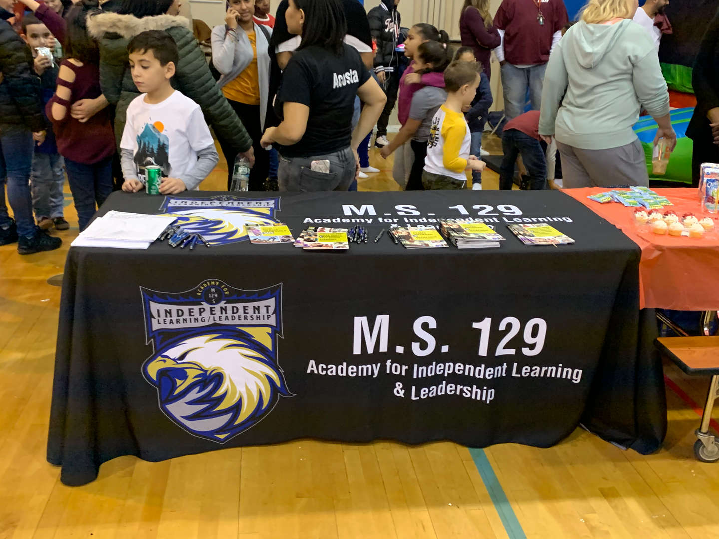 People gathered around the M.S. 129 Academy for Independent Learning & Leadership table