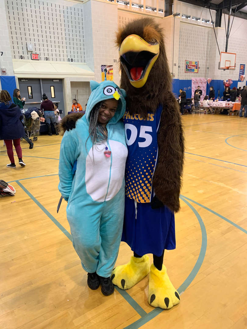 A student in a colorful onesie stands with the school mascot
