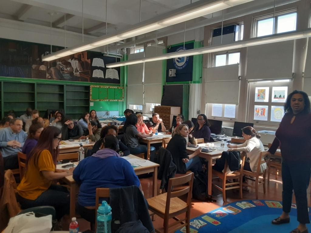 A classroom of adults fill out worksheets while listening to a woman speak