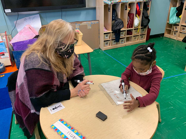 Teacher helps a student with the alphabet