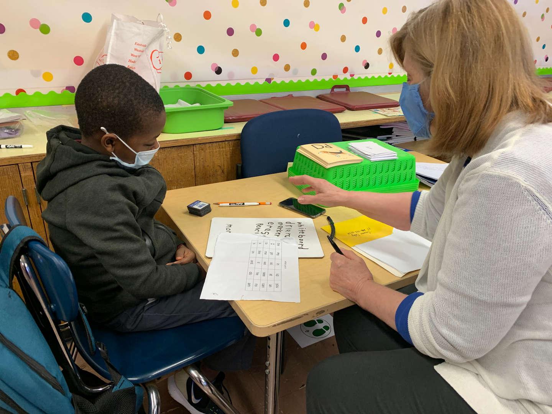 Teacher works with boy on reading skills