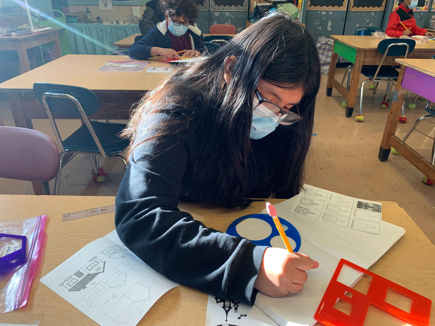 Girl wearing face mask uses drawing stencils
