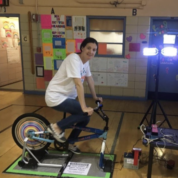Student smiling on a stationary bike