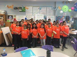 A class of students wearing matching orange shirts