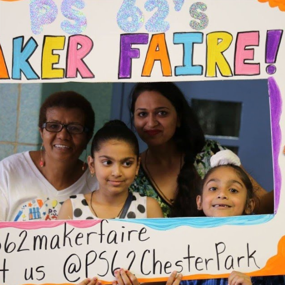 Students and their teachers holding up a Maker Faire sign