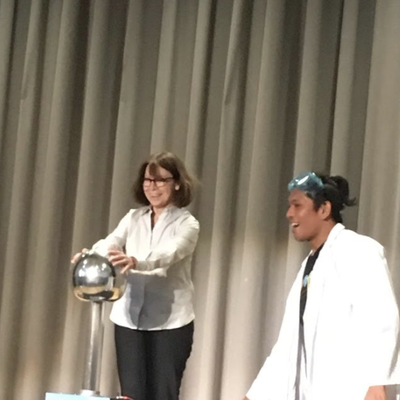 Man in a lab coat stands with a woman on stage