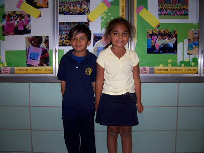 Boy wearing all navy and girl wearing a pale yellow polo and skirt