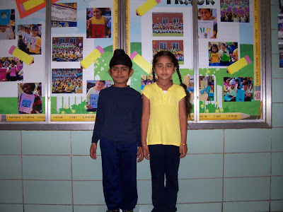 Boy wearing all navy and girl wearing a yellow top and dark bottoms