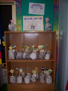 A shelf with jars of students' handmade crafts