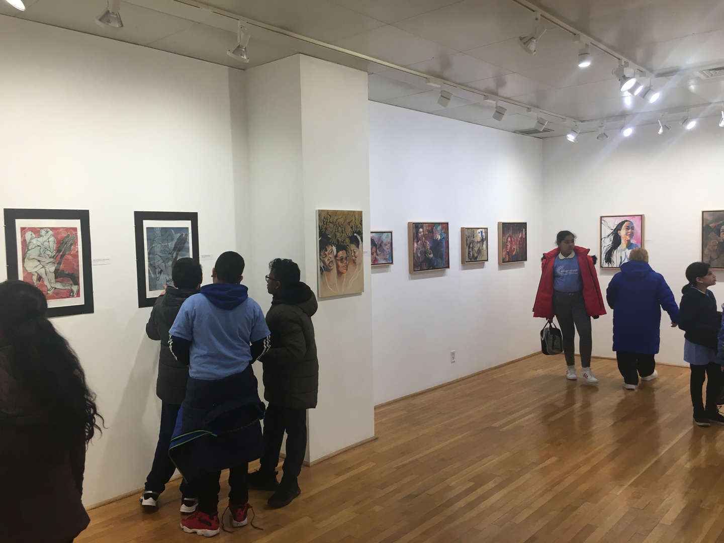 Students admire artwork on the walls of an exhibit