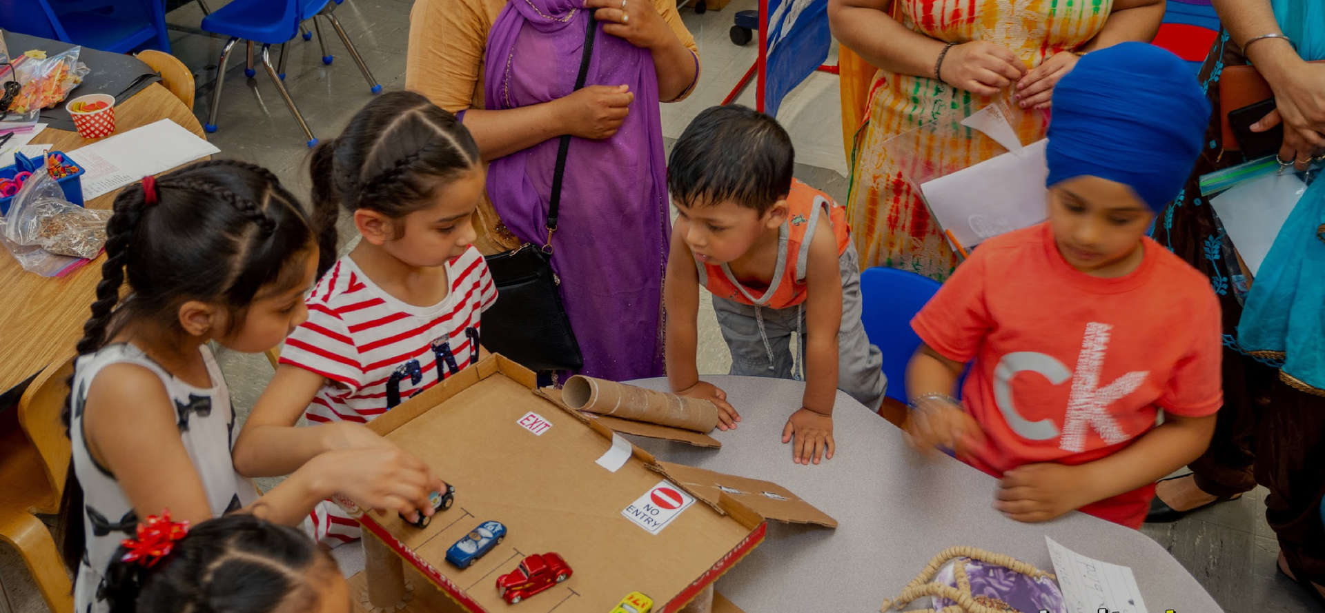 Students playing with toy cars on a cardboard ramp