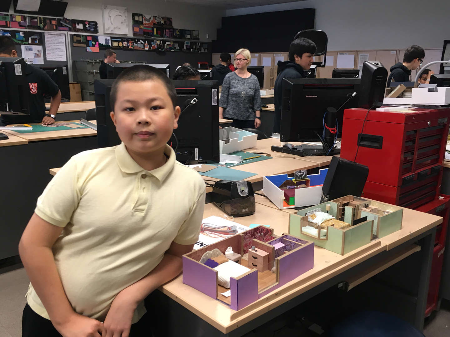 A student poses next to a diorama of a house
