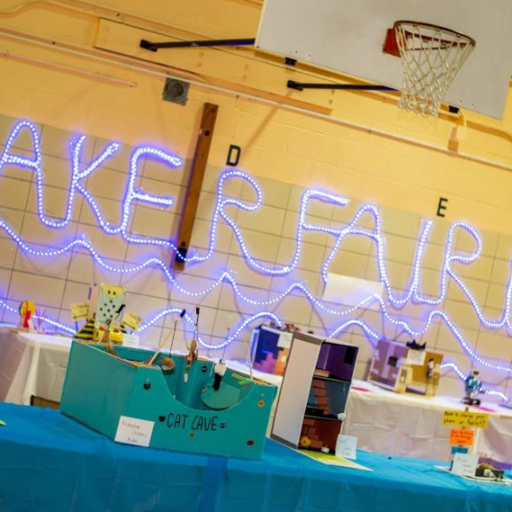 Light strips spelling out Maker Faire on the gymnasium wall