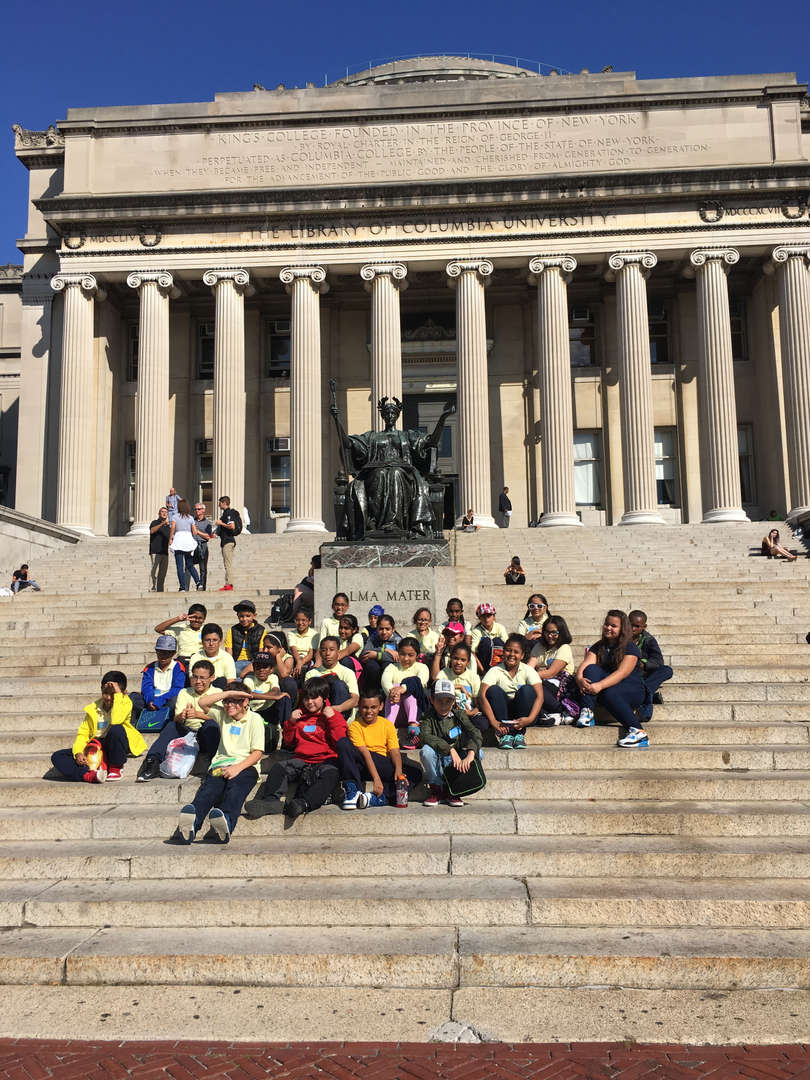 Students sitting on the steps of the Columbia University library