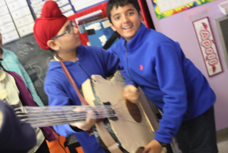 Two students playing a guitar made of cardboard