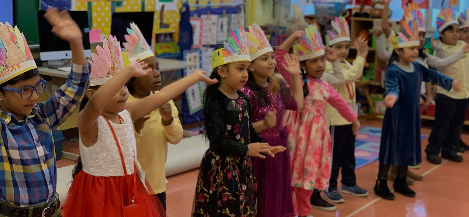 Students wearing paper headdresses dancing in class