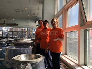 Three teachers standing behind trash cans in front of a wall of windows