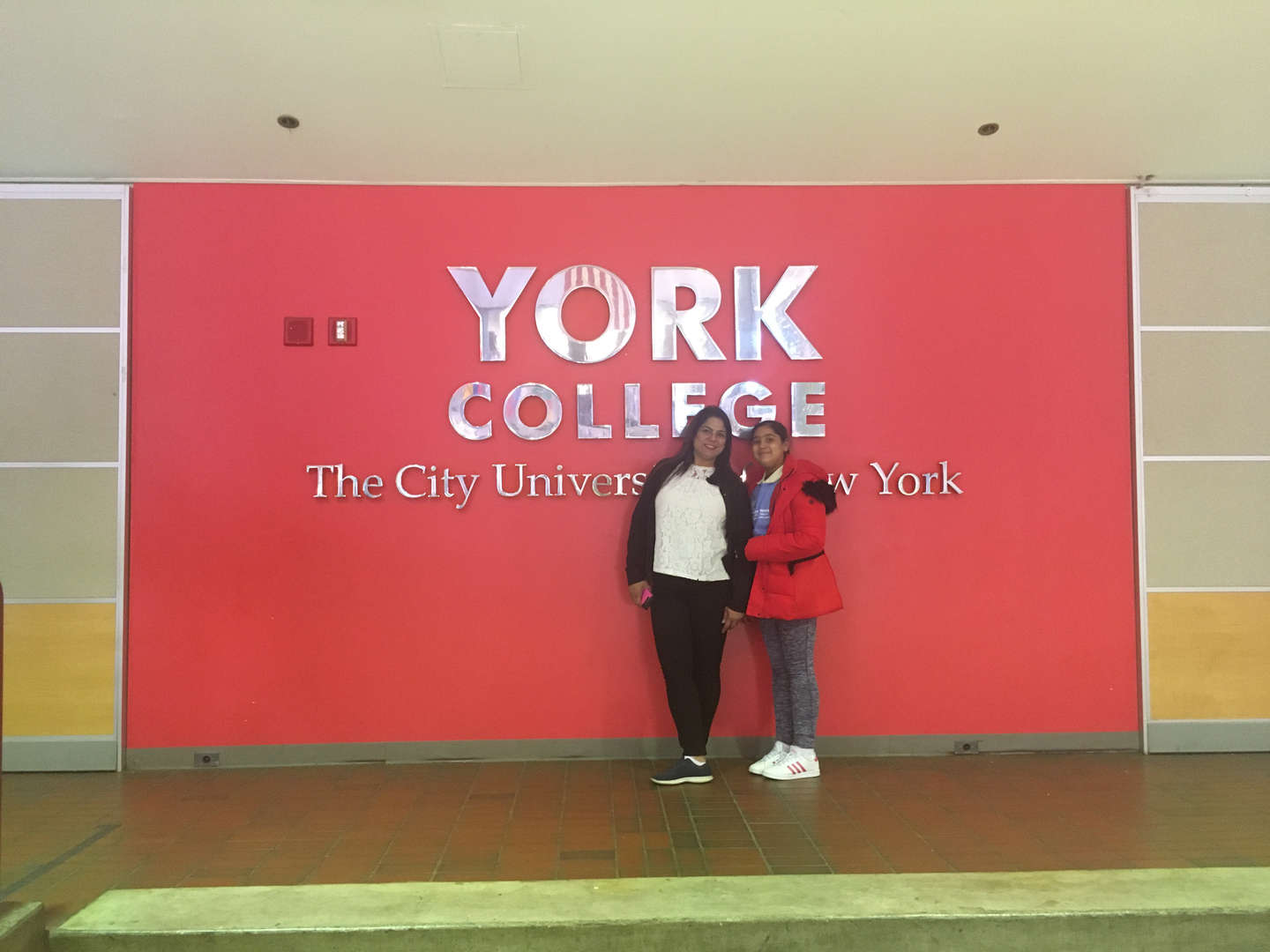 Two students in front of the York College sign