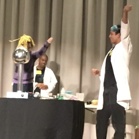 Two people in lab coats hold up their arms beside their experiment