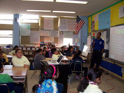 A NYPD school officer speaks to students at the front of the classroom